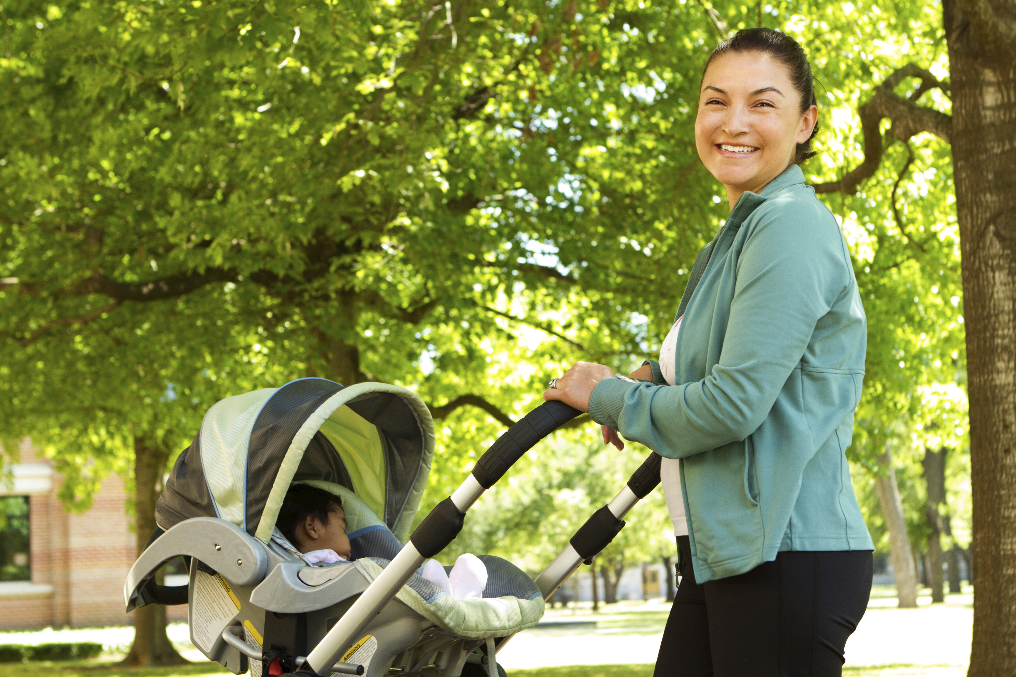 Smiling mother taking baby for walk on campus.